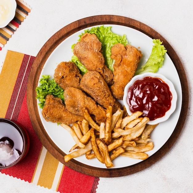 Close-up di pollo fritto e patatine fritte Foto Gratuite