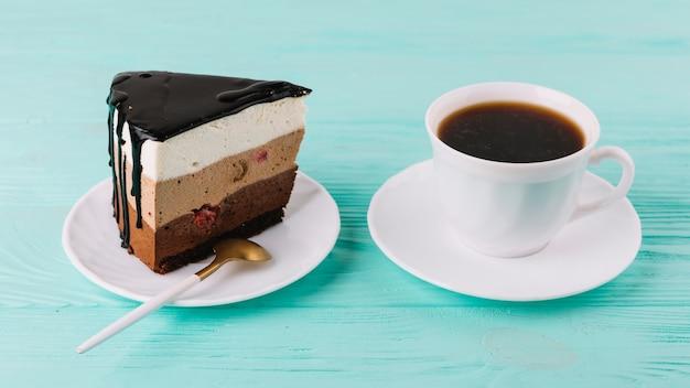 Close-up di una gustosa torta cremosa con cucchiaio e tazza di tè Foto Gratuite