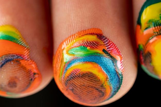 Close-up di vernice mista sulle dita Foto Gratuite