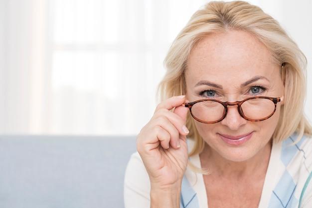 Close-up donna con gli occhiali al chiuso Foto Gratuite