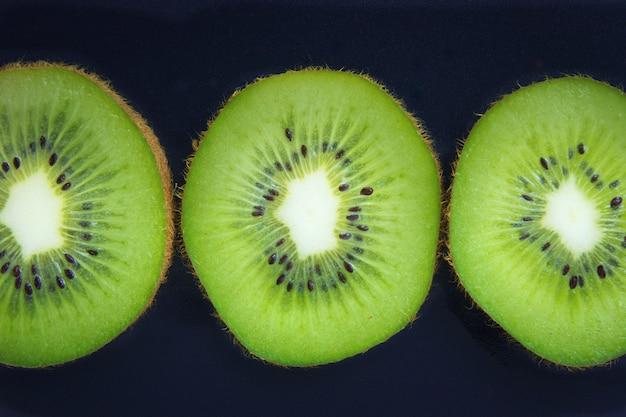 Close up fette organiche kiwi su sfondo nero Foto Premium