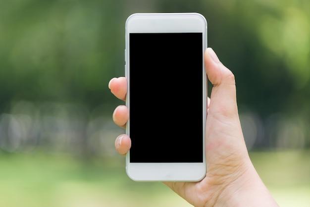 Close-up mano mostrando sul telefono mobile nero vuoto schermo concetto di lifestyle all'aperto sullo sfondo sfocato della natura - può essere utilizzato immagine imbrattata. immagini di stile d'effetto vintage. Foto Gratuite
