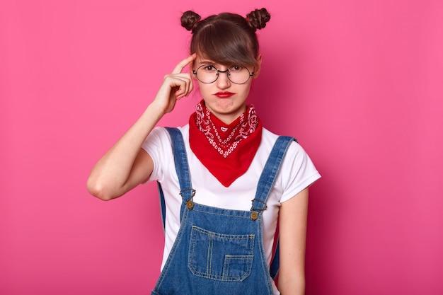 Close up ritratto di studentessa bruna, indossa occhiali rotondi e bandana rossa sul collo, curva le labbra, tiene il dito anteriore sul tempio Foto Gratuite
