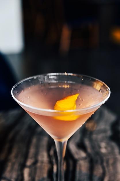 Close-up rosa cocktail riempito una fetta di buccia di yuzu in bicchiere di vino sul tavolo in marmo. Foto Premium