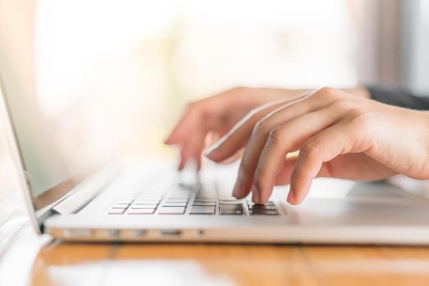 Closeup della donna d'affari digitando sulla tastiera del computer portatile. Foto Gratuite