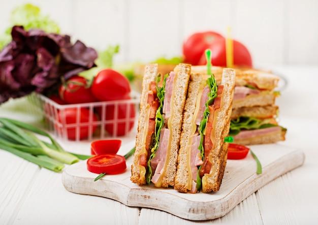 Club sandwich - panini con prosciutto, formaggio, pomodoro ed erbe. vista dall'alto Foto Gratuite