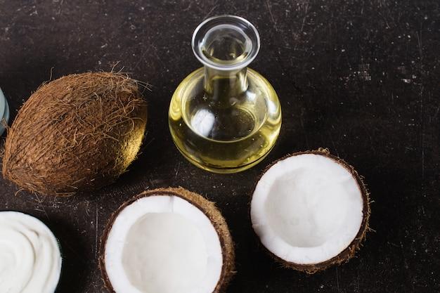 Cocco e olio di cocco su uno sfondo di marmo scuro. grande noce esotica. cura personale. trattamenti spa Foto Premium