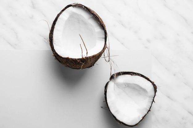 Cocco fresco tagliato a metà su sfondo bianco e marmo Foto Gratuite