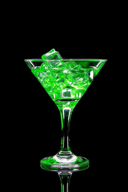 Cocktail del martini con ghiaccio e gli indicatori luminosi verdi sul nero Foto Premium