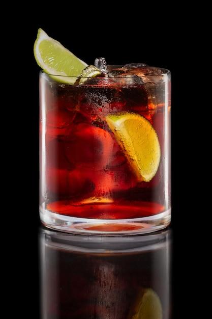 Cocktail del rum e della cola in vetro delle rocce isolato sul nero Foto Premium