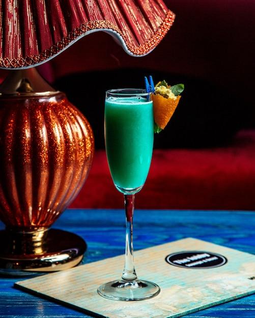 Cocktail dell'alcool con scorza d'arancia e vista laterale dei fiori Foto Gratuite