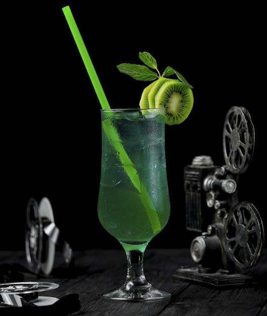 Cocktail dell'alcool del kiwi con le fette della frutta e il tubo verde. Foto Gratuite