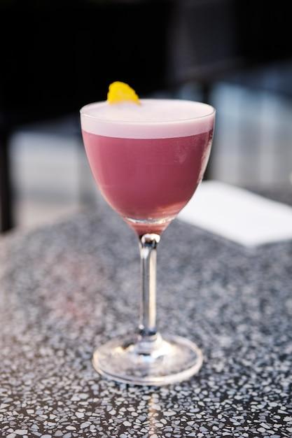 Cocktail di brandy alla ciliegia sul tavolo sulla terrazza all'aperto (foto con profondità di campo) Foto Premium