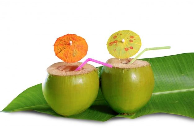 Cocktail di paglia di cocco bevanda sulla foglia di albero di banane Foto Premium