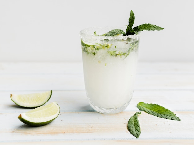 Cocktail freddo bianco con menta, lime e ghiaccio in studio Foto Gratuite