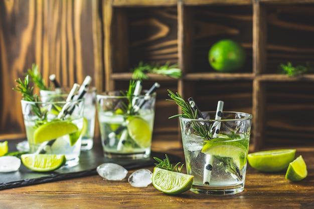 Cocktail fresco con lime, ghiaccio e rosmarino, cocktail mojito Foto Premium