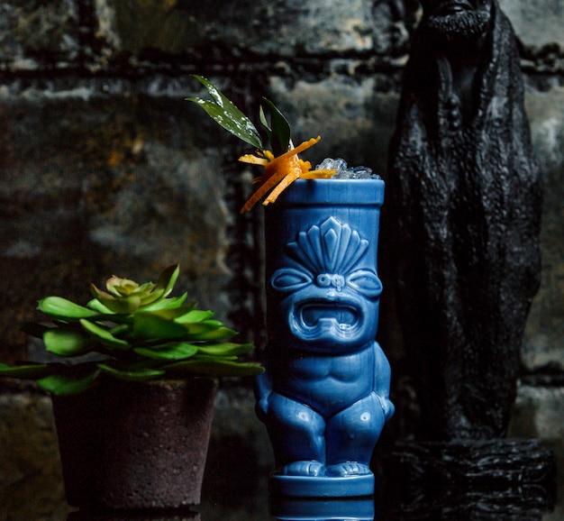 Cocktail guarnito con l'arancia in tazza blu del cocktail Foto Gratuite