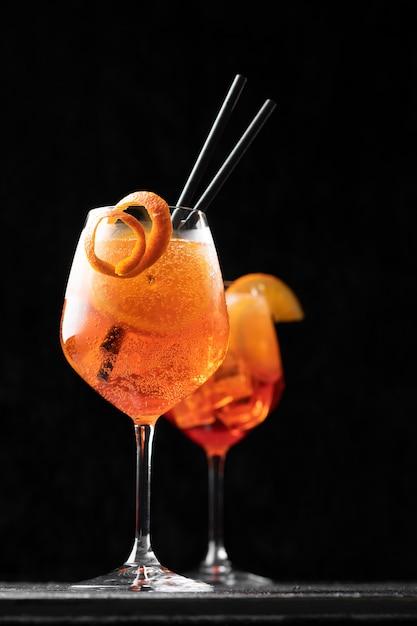 Cocktail italiano classico dello spritz dell'aperol in vetro sul nero, fine su Foto Premium