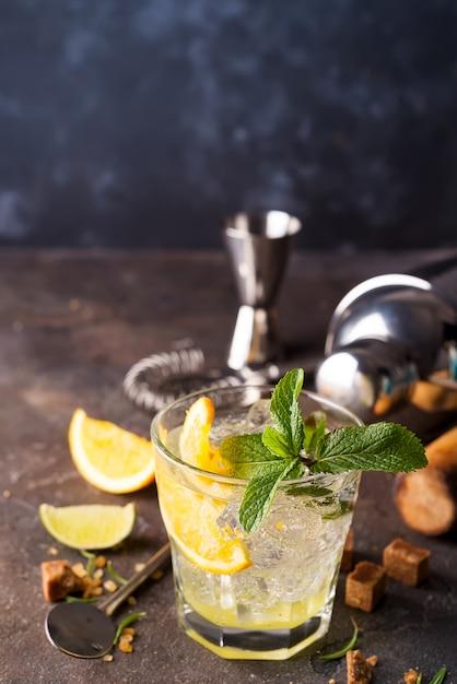 Cocktail mojito o caipirinha. zucchero bruno e un bicchiere vuoto su pietra Foto Premium