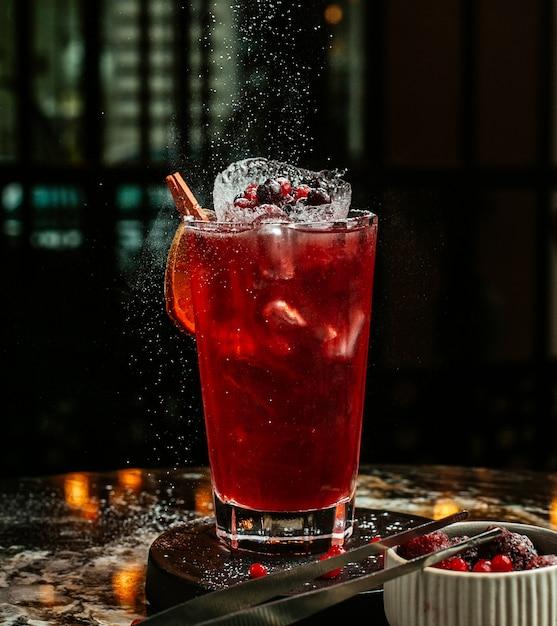 Cocktail rosso con cubetti di ghiaccio e bacche. Foto Gratuite