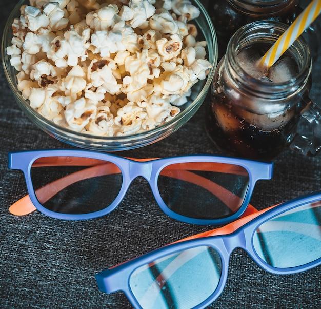 Cola con ghiaccio, popcorn in una ciotola trasparente e occhiali 3d Foto Premium