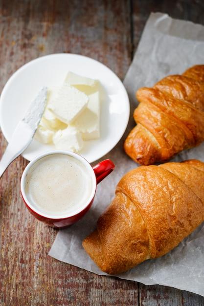 Colazione a base di una tazza di caffè e cornetti al burro Foto Premium