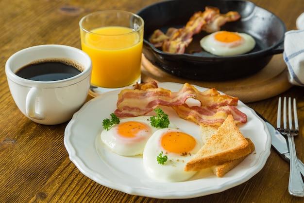 Colazione all'americana con uova, pancetta, toast, pancake, caffè e succo Foto Premium