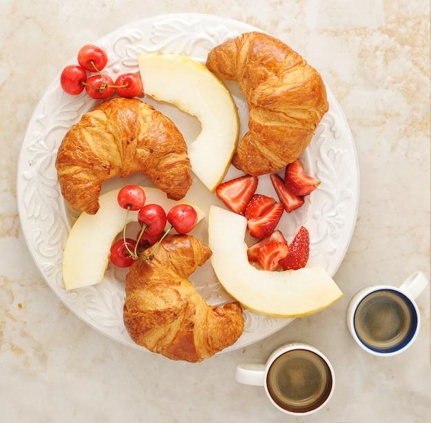 Colazione con caffè, cornetti e frutta - melone, fragole, ciliegie Foto Premium