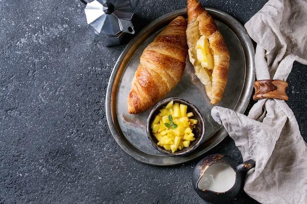 Colazione con croissant e frutta di mango Foto Premium