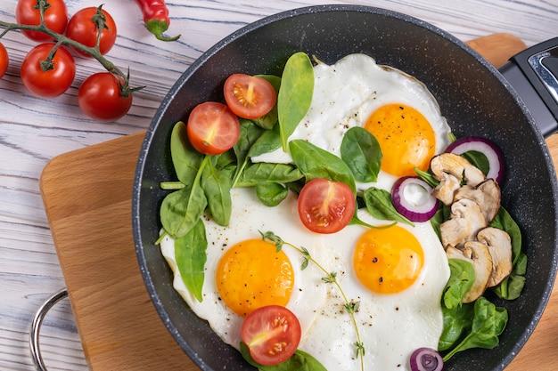 Colazione con uova, pomodori con funghi e foglie di spinaci freschi Foto Premium