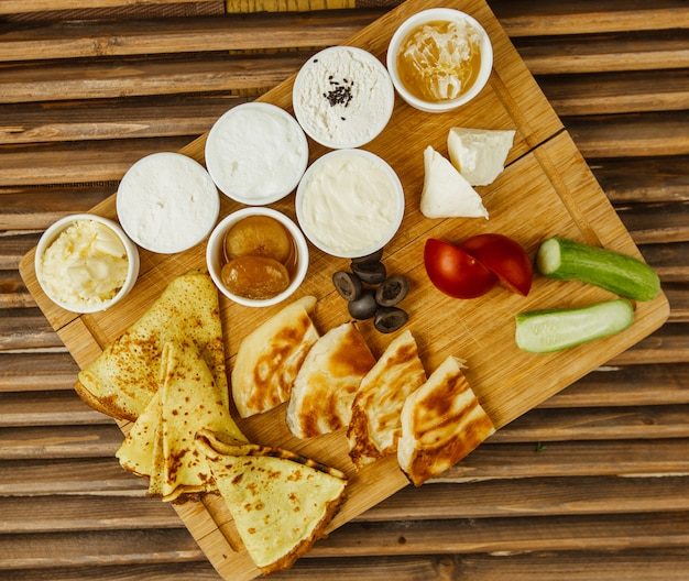 Colazione in legno con crepes, miele, crema di formaggio, verdure e confettura Foto Gratuite