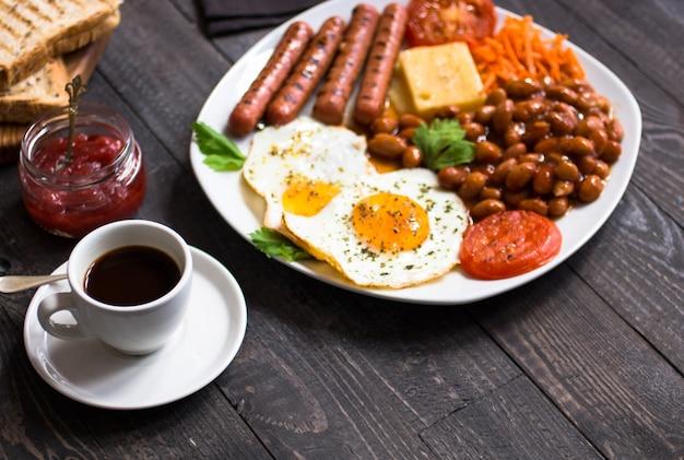 Colazione inglese. uova fritte, salsicce, fagioli, toast di pane, pomodori, formaggio, Foto Premium