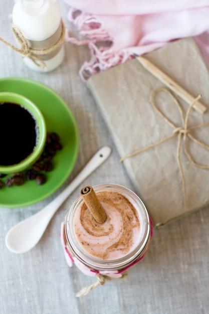 Colazione nutriente: farina d'avena con yogurt ai frutti di bosco e cannella, caffè nero e una bottiglia di latte. Foto Premium