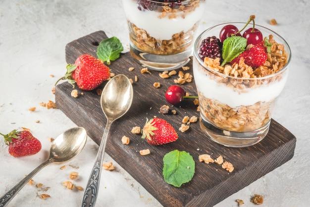Colazione salutare. frutti e bacche estive. yogurt greco fatto in casa con muesli, more, fragole, ciliegie e menta. sul tavolo di pietra bianca di cemento, in bicchieri. Foto Premium