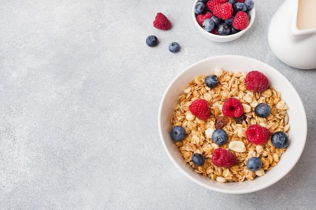 Colazione salutare. muesli fresco, muesli con yogurt e frutti di bosco su sfondo grigio. Foto Premium