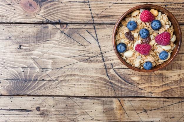 Colazione salutare. muesli fresco, muesli con yogurt e frutti di bosco su superficie di legno Foto Premium