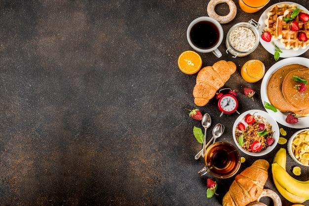 Colazione sana mangiare concetto, vari cibi mattutini - frittelle, cialde, cornetti sandwich di farina d'avena e muesli con yogurt, frutta, bacche, caffè, tè, succo d'arancia Foto Premium