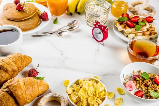 Colazione sana mangiare concetto vari cibi mattutini - frittelle cialde croissant farina d'avena sandwich e muesli con yogurt frutta bacche caffè tè succo d'arancia sfondo bianco Foto Premium