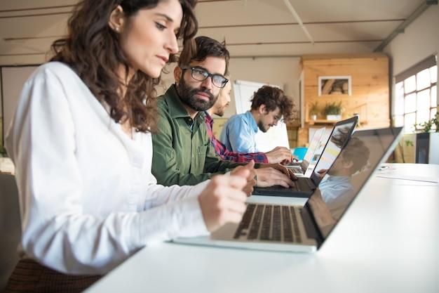 Collaboratori seri con i computer portatili che discutono progetto Foto Gratuite
