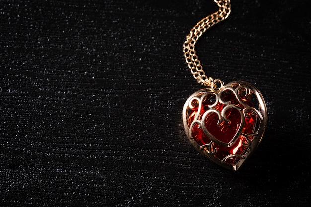 Collana d'oro con diamante cuore rosso su sfondo nero Foto Premium