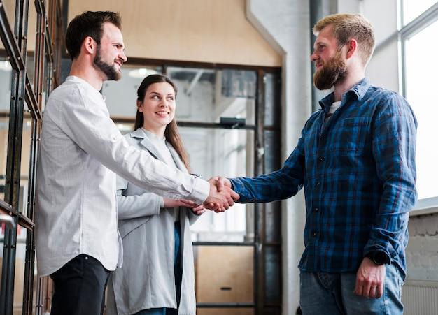 Collega maschio due che stringe mano davanti alla donna di affari sorridente in ufficio Foto Gratuite