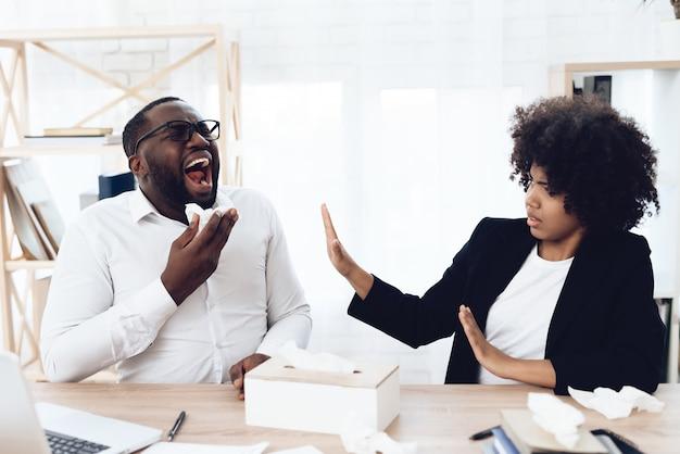 Colleghe africani che si siedono al tavolo con l'uomo che starnutisce. Foto Premium