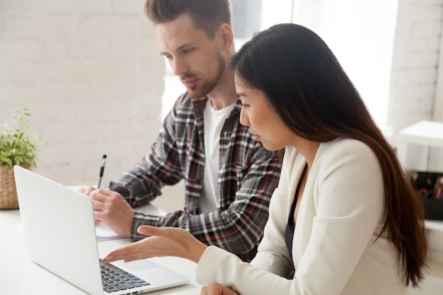 Colleghi asiatici e caucasici che lavorano insieme a discutere di attività con il computer portatile Foto Gratuite