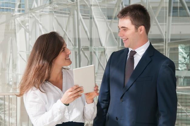 Colleghi che sorridono, donna che mostra i dati sul ridurre in pani Foto Gratuite