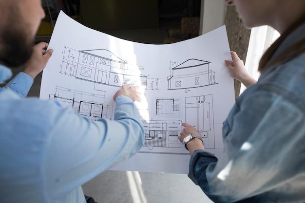 Colleghi che tengono il modello e che discutono sul progetto all'ufficio Foto Gratuite