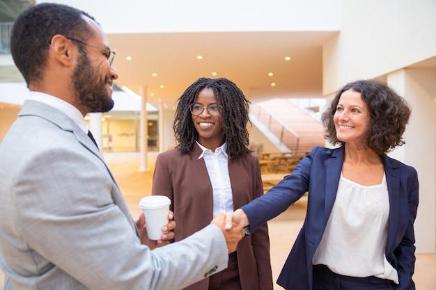 Colleghi felici di affari che si salutano nel corridoio Foto Gratuite