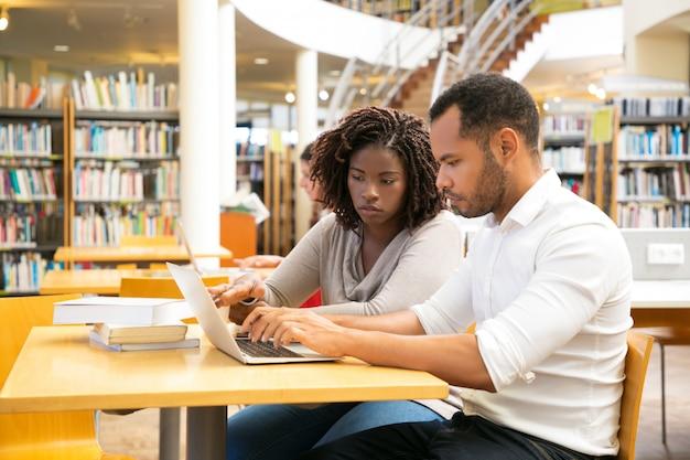 Colleghi seduti in biblioteca e usando il portatile Foto Gratuite
