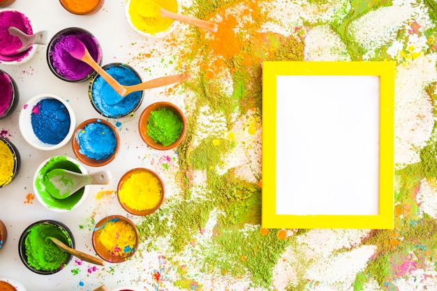 Collezione di ciotole con colori secchi brillanti vicino a telaio e pile di colori Foto Gratuite