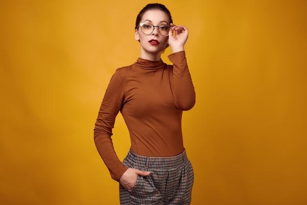 Collo alto e vetri d'uso della donna castana di modo su fondo giallo Foto Premium