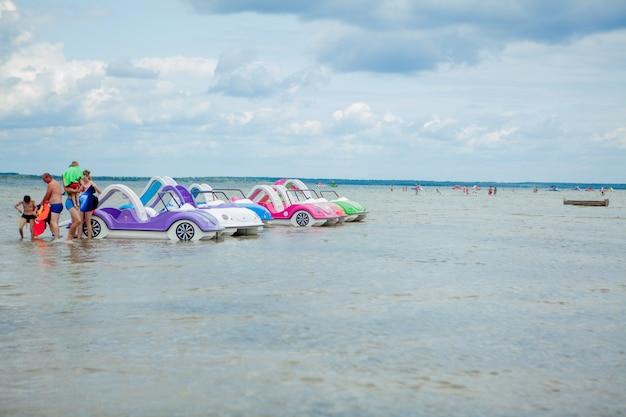 Colorati vecchi catamarani di plastica vintage e barche vicino a un molo di legno sulla riva di un grande lago Foto Premium